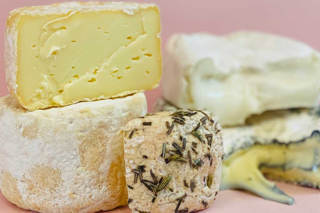 A collection of cheeses including yellow cheese, soft cheese and blue cheese