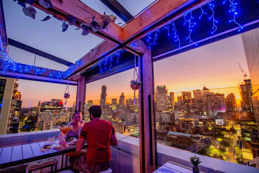 Two people on a rooftop bar at sunset