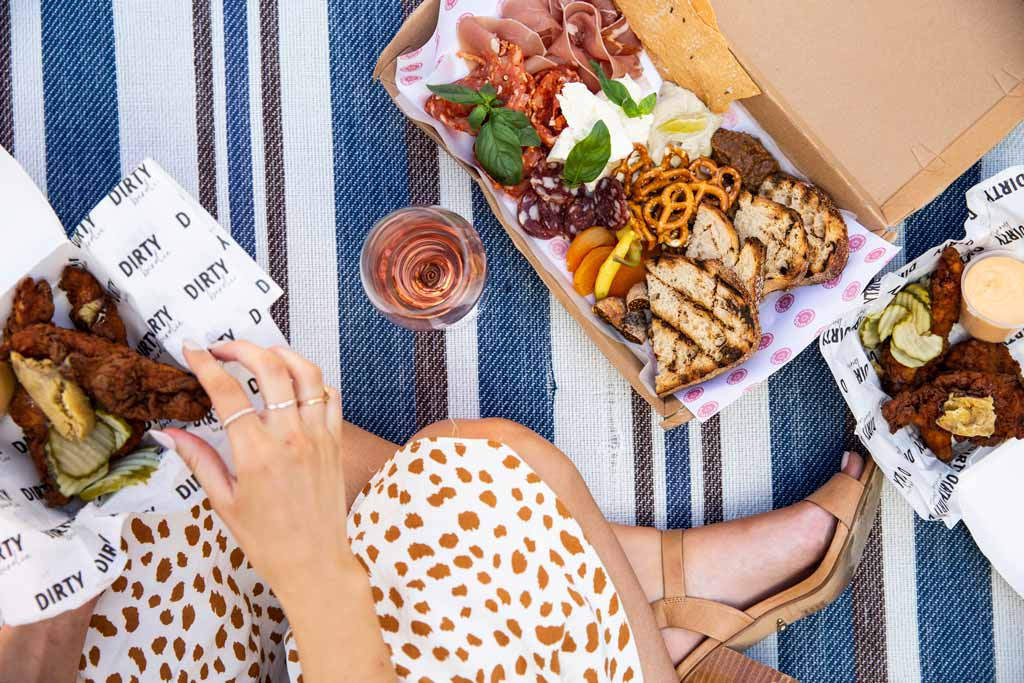 A picnic rug with food and wine on it