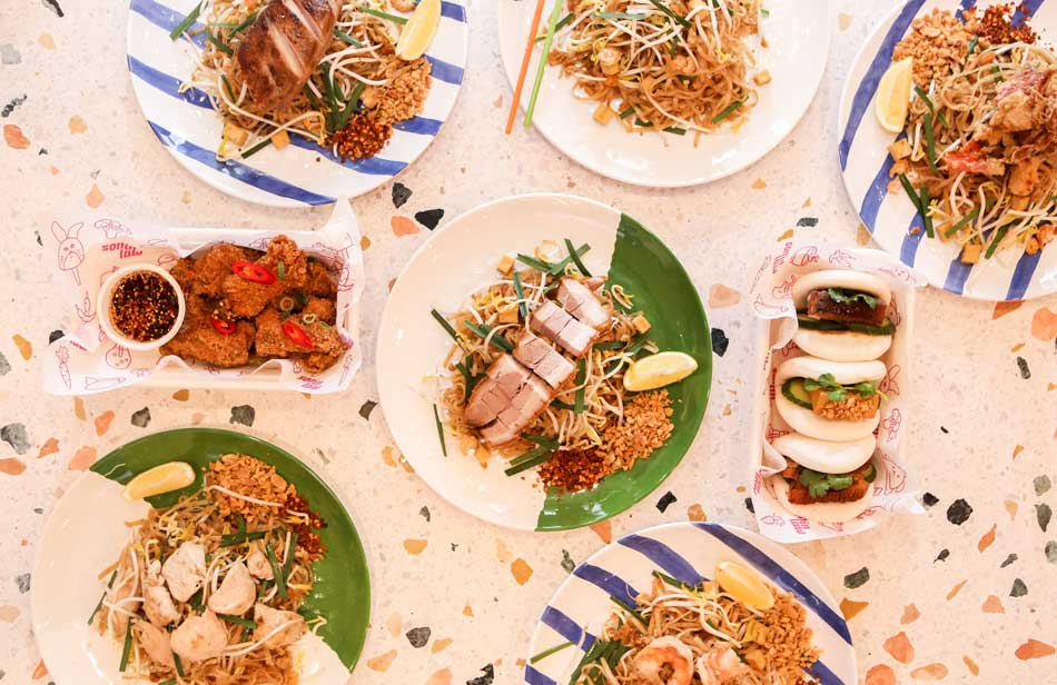 Thai food on a pale pink table