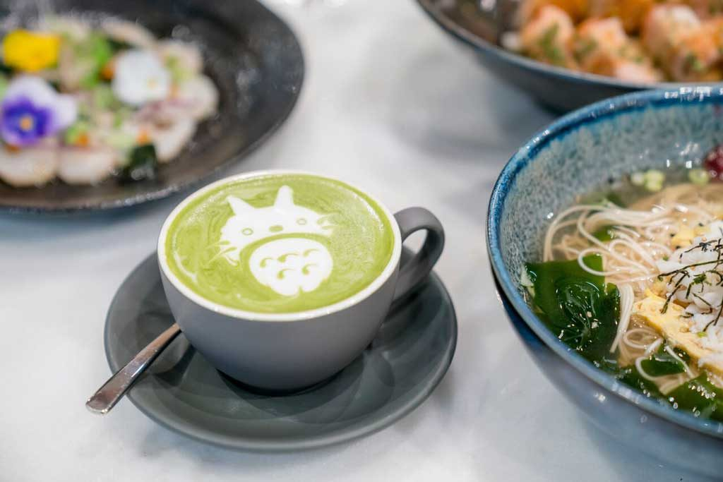A green drink in a mug with latte art on top