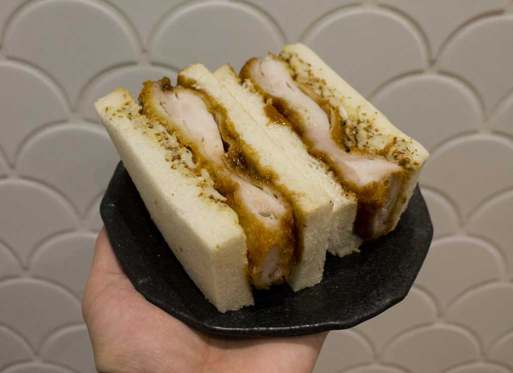 A chicken sandwich on white bread on a black plate