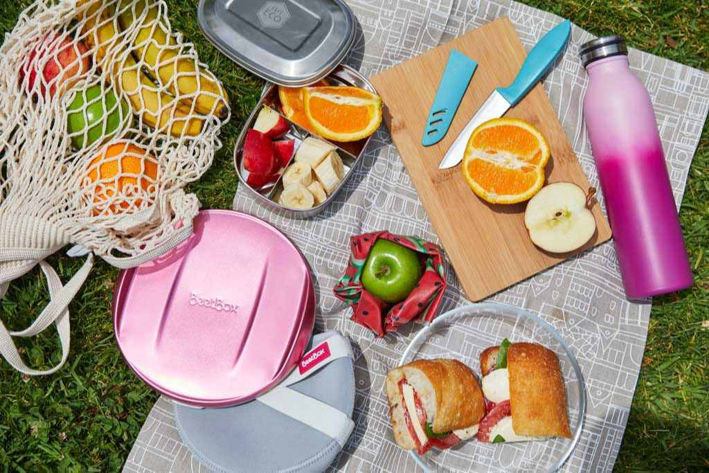 Food and fruit on a picnic mat on the grass