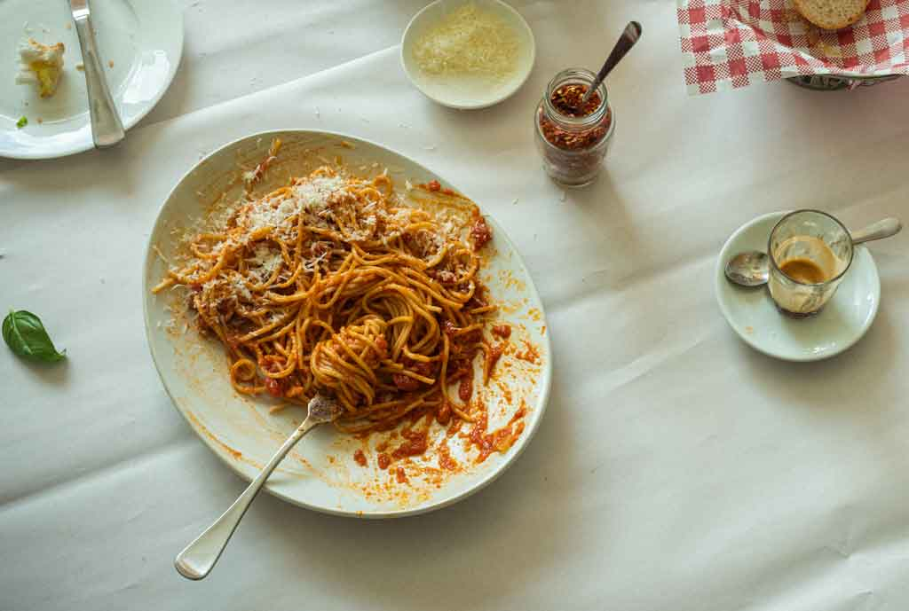 A white plate with spaghetti on it on a white table