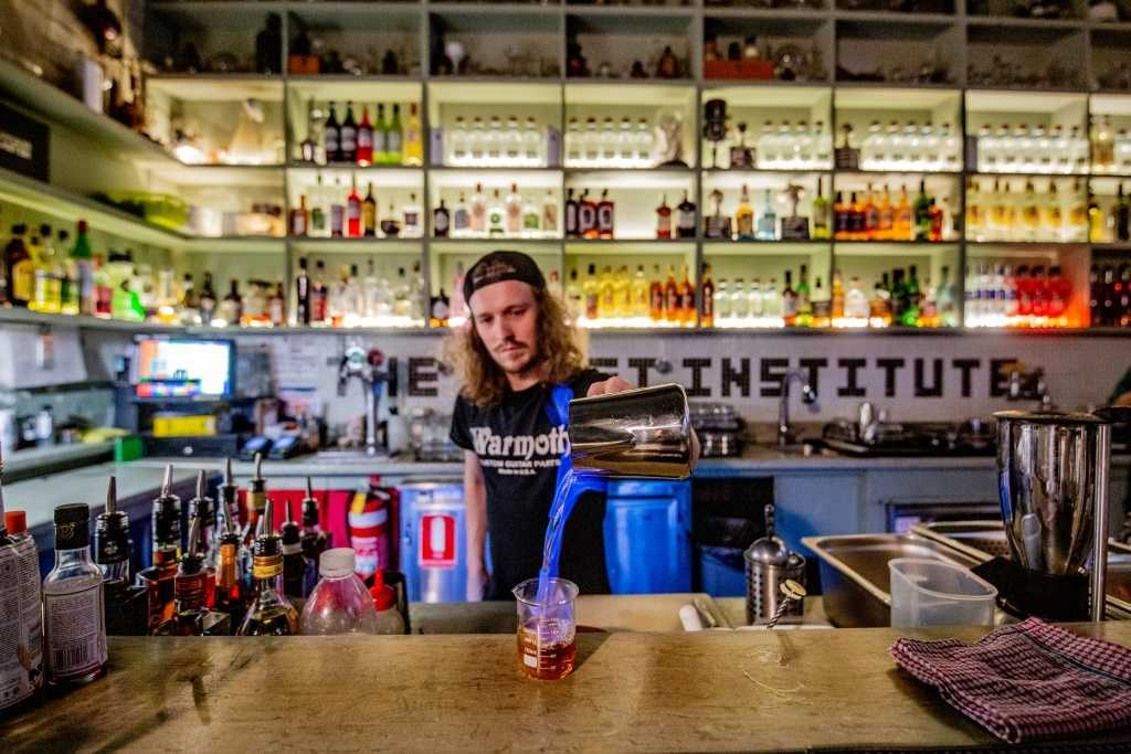 A bartender pouring a theatrical drink at the bar
