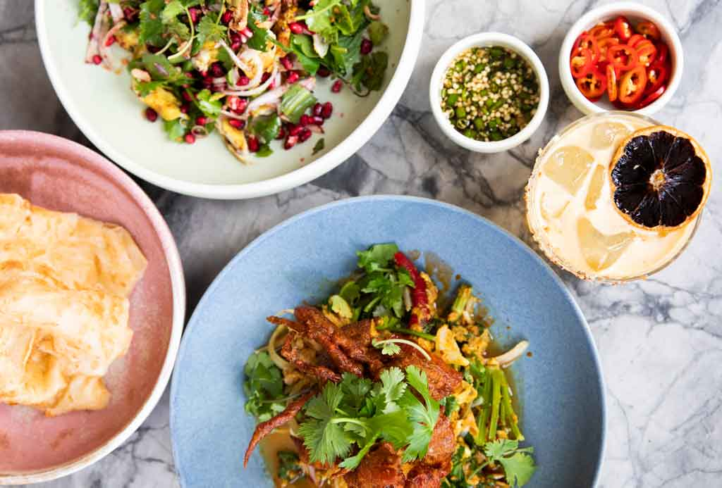 A range of colourful Thai food dishes on a white table