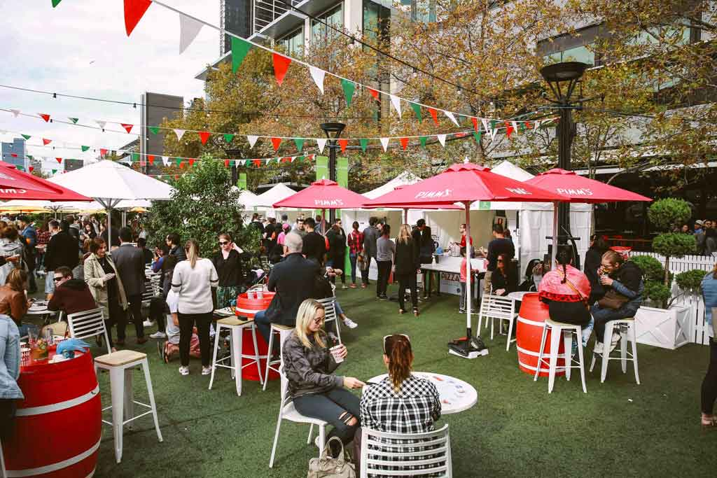 An outdoor foodie event with different coloured bunting hanging over tables