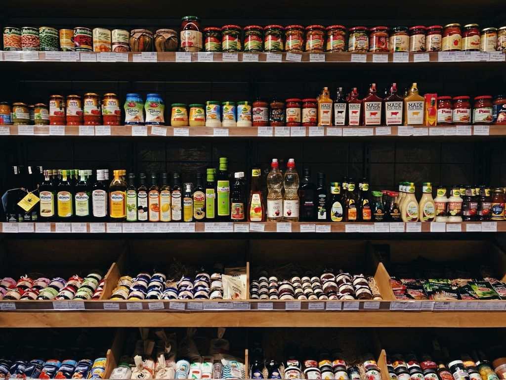 Shelves full of sauce bottles and produce