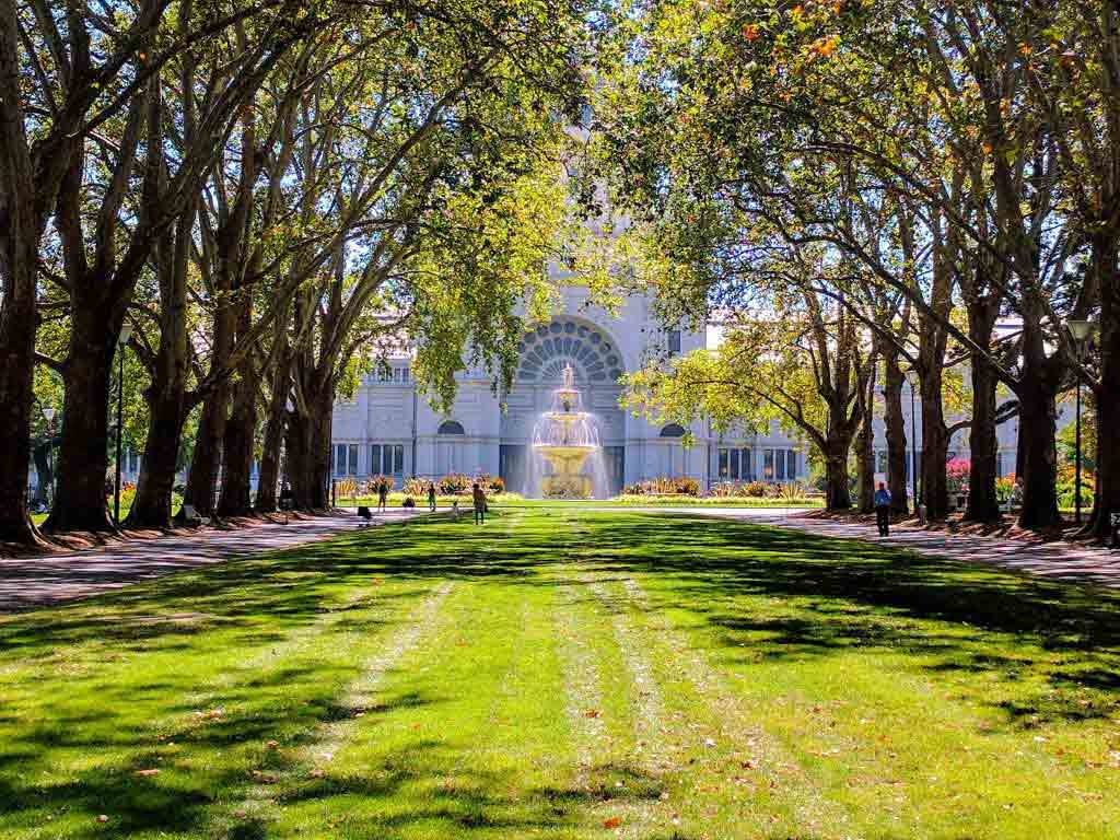 Tree-lined Carlton Gardens lawn and Royal Exhibition Building