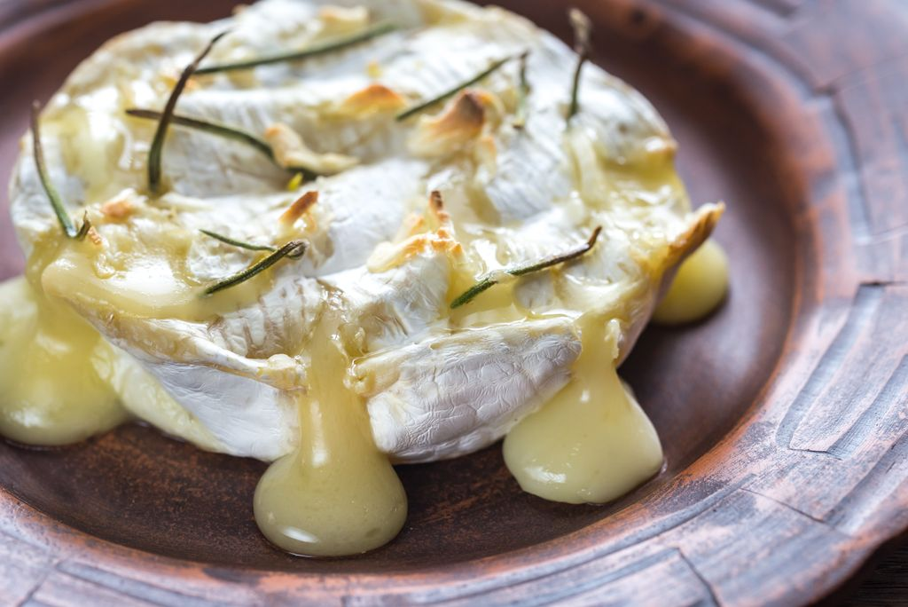 A melting wheel of cheese with rosemary garnish