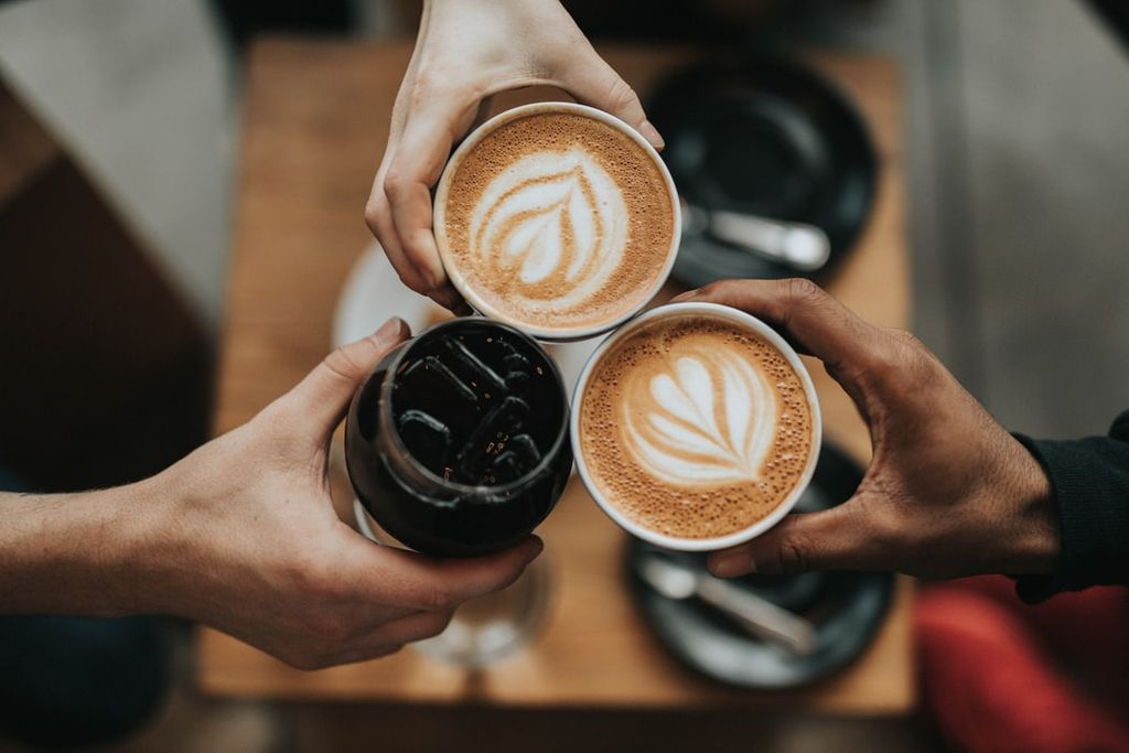People holding out coffee cups together in a cheers