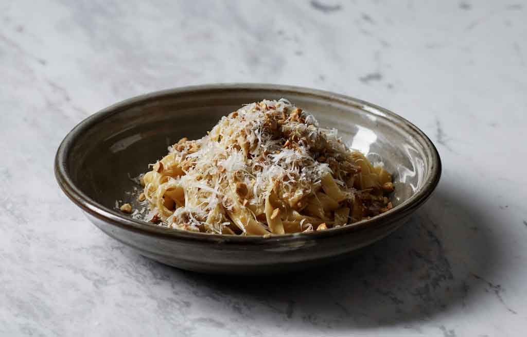 A bowl of pasta on a marble table