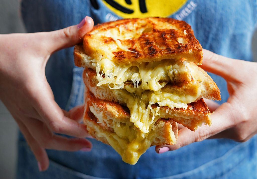 A person holding a stack of cheese toasties