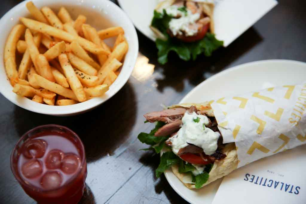 A bowl of fries on a table with a red drink and a souvlaki on a plate next to it