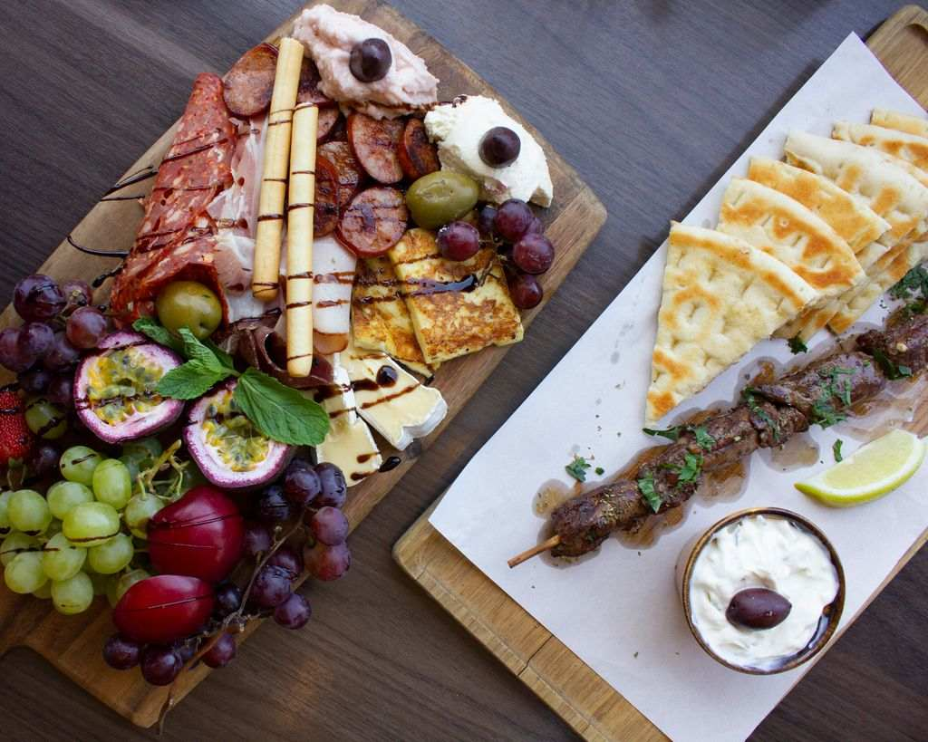 Two platter of Greek food on a table