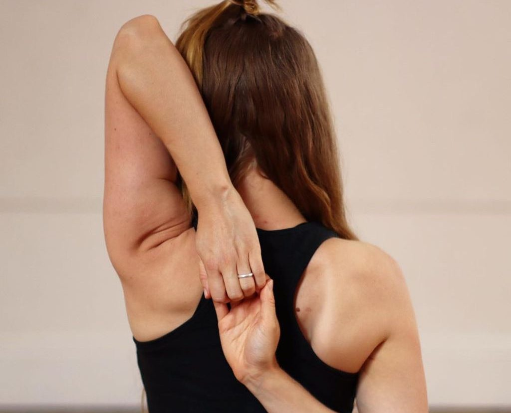 Person clasping hands behind back in yoga pose