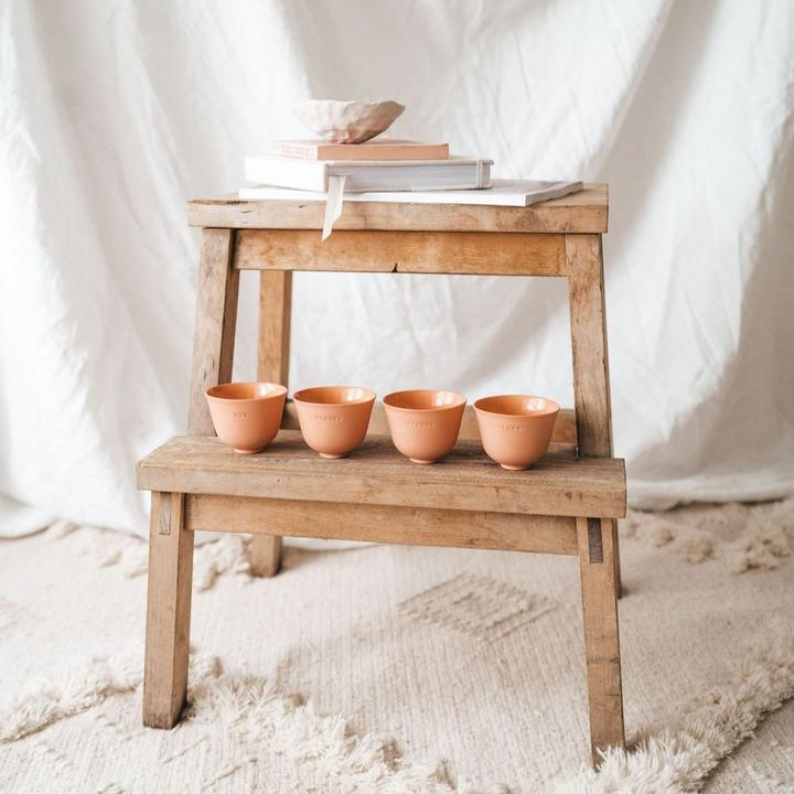 A wooden stool with cups and books styled on it