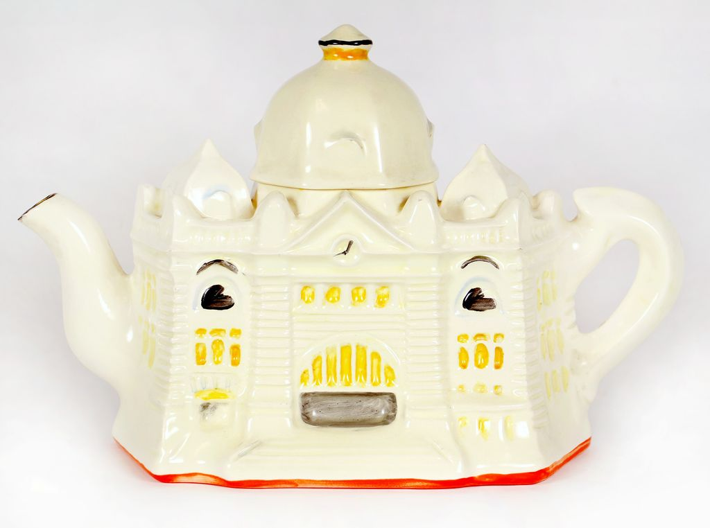 A ceramic teapot in the shape of Flinders Street station with eyes and mouth