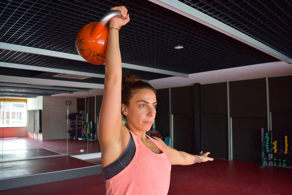 Person lifting a kettle bell weight in a gym