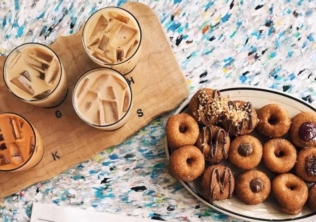 A wooden tray with glasses of iced coffee on it next to a wooden tray of doughnuts