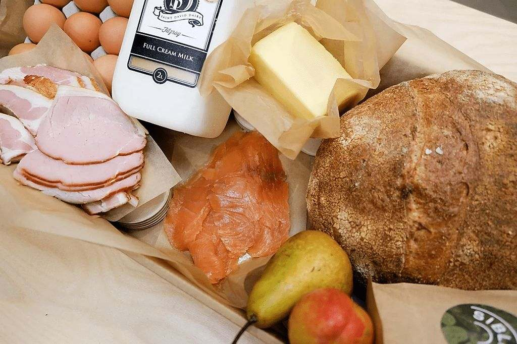 Bread, butter, bacon, eggs, milk, smoked salmon and pears sitting in brown paper in Kinfolks hamper