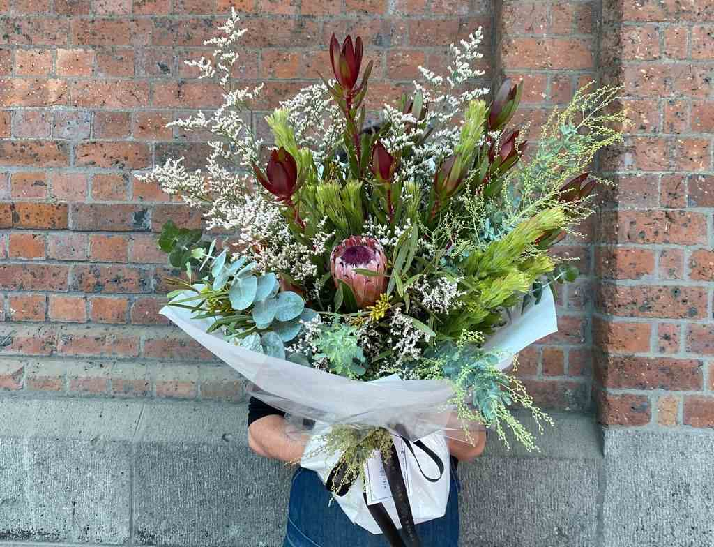 A person holding a bouquet of flowers in front of them