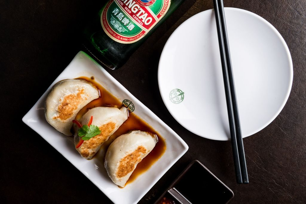 Dumplings on a small plate next to a beer
