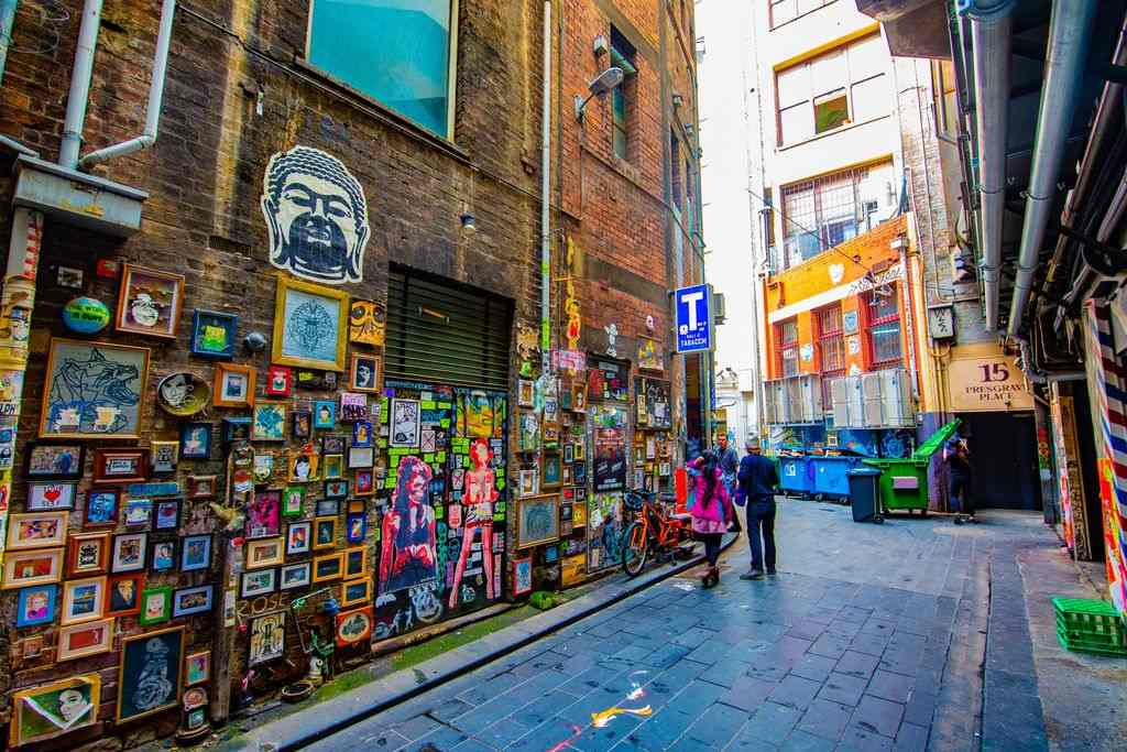 A laneway with a brick wall covered in photo frames and artwork