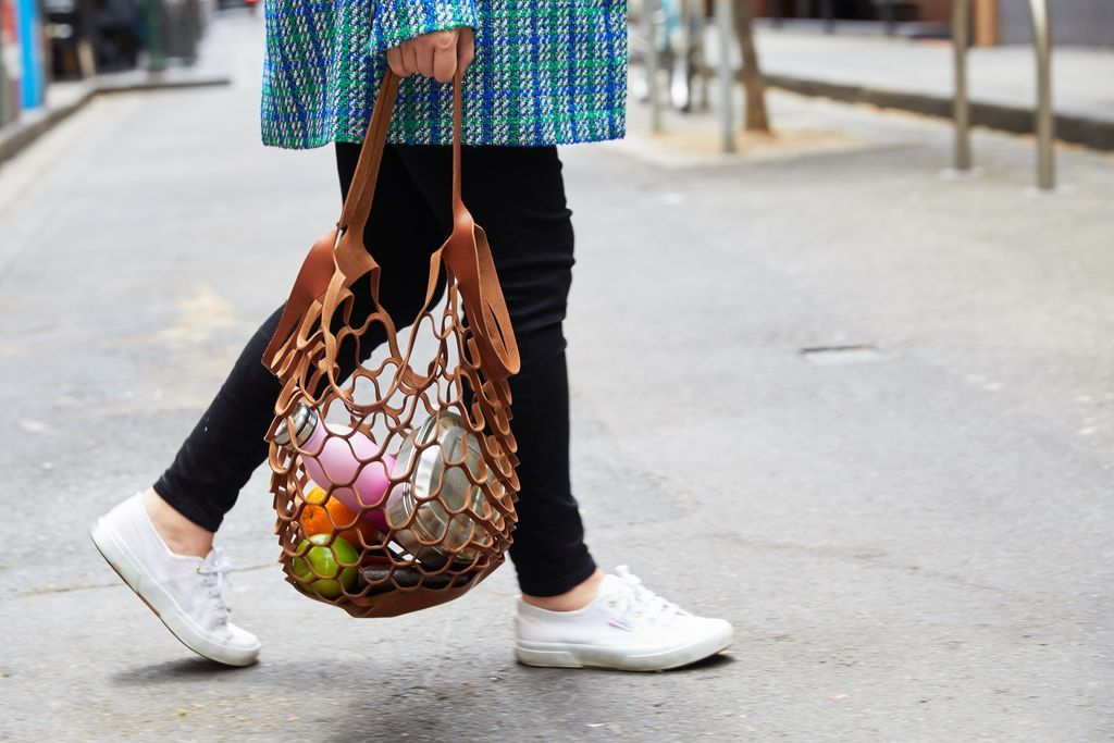 A woman holding a netted shopping bag