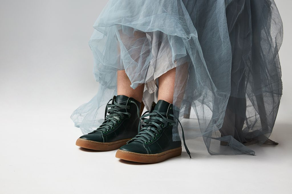 A woman in a tutu wearing a pair of green sneakers