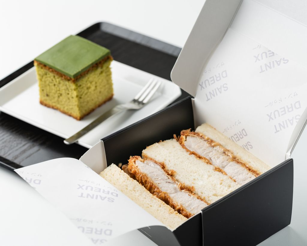 A sandwich in a box next to a cake in a box