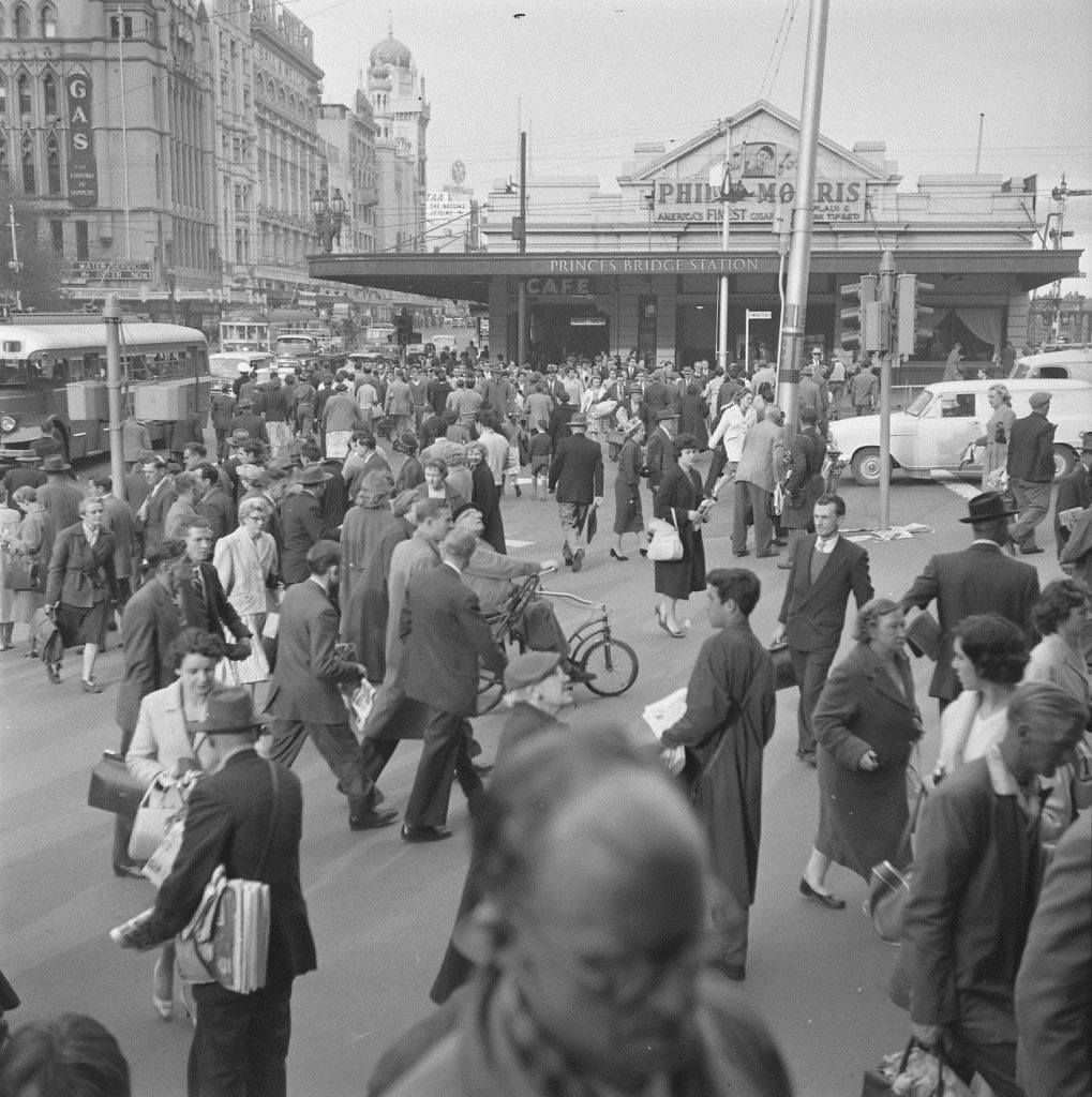 A black and white photo of people entering a crowded train station
