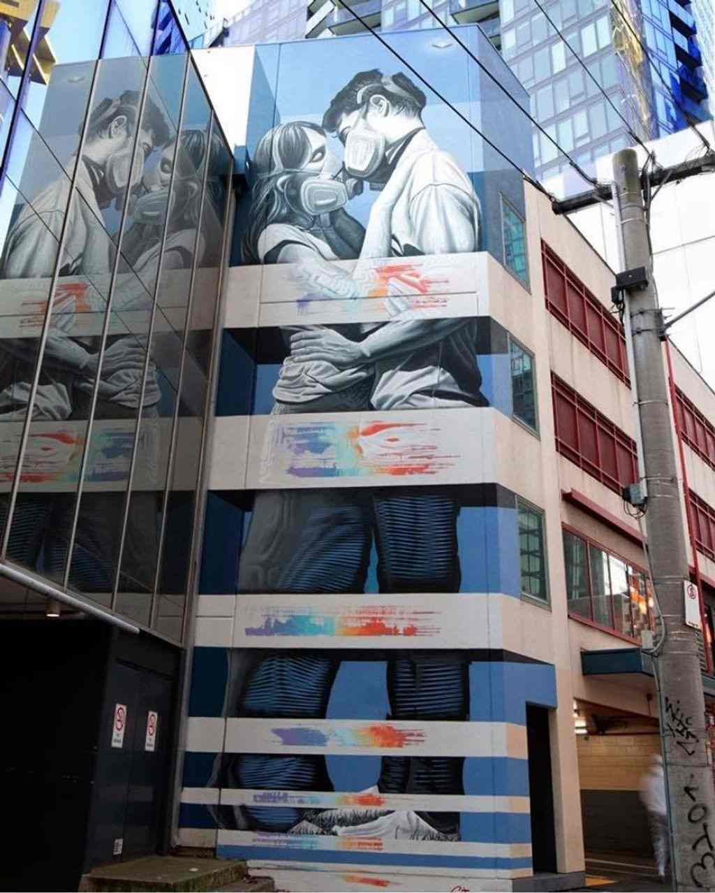 A mural of two people embracing wearing masks