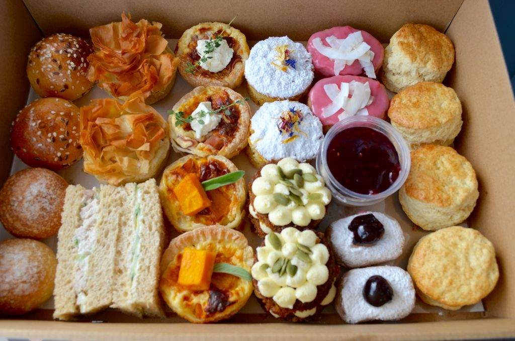 A box filled with sandwiches and pastries