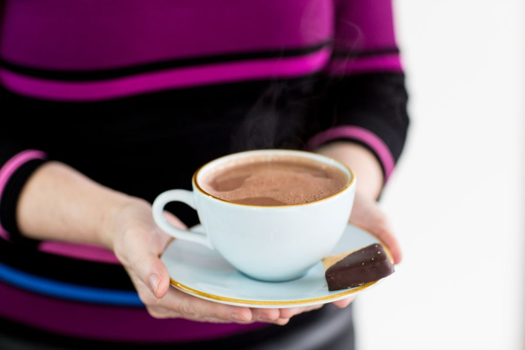 A woman holding out a mug of hot chocolate on a saucer