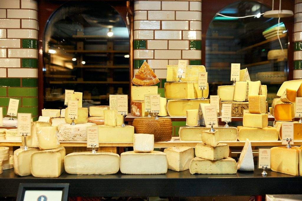 A stack of different cheeses in a shop
