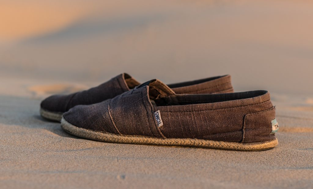 A pair of canvas slip on shoes on some sand