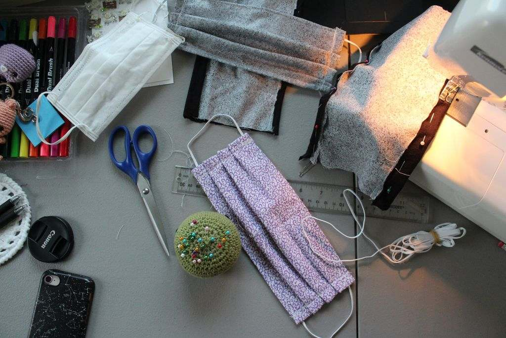 A craft table with pins and fabric on it