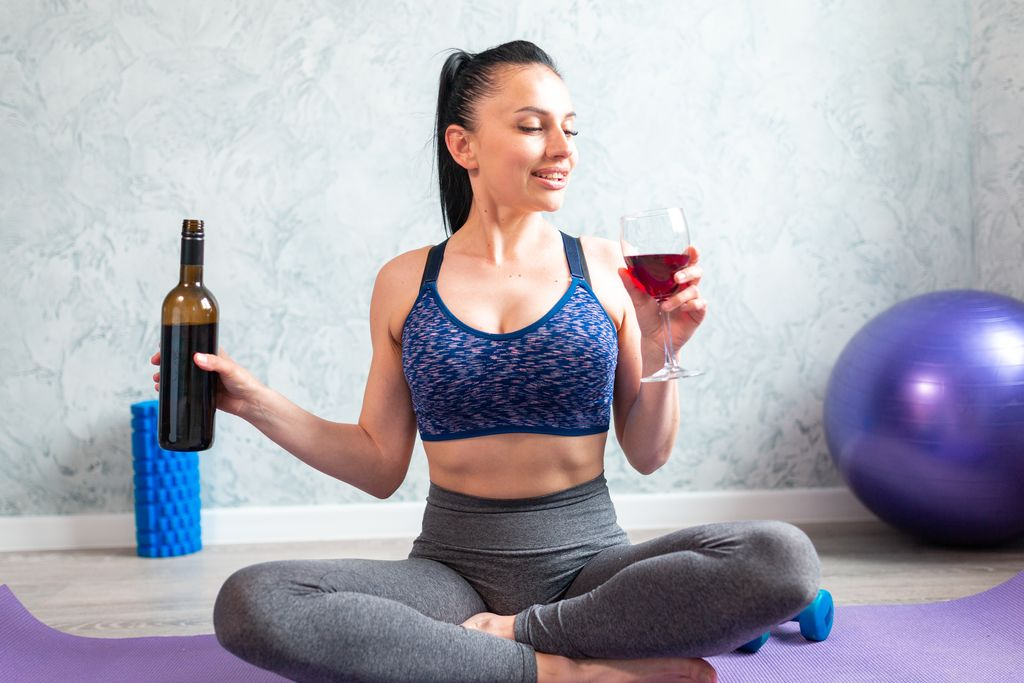 A woman drinking wine on a yoga mat