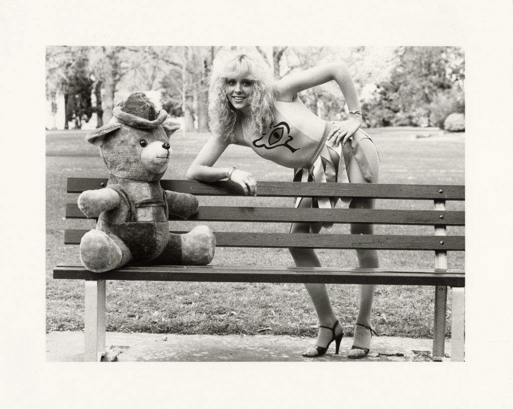 A woman in a bikini leaning over a park bench