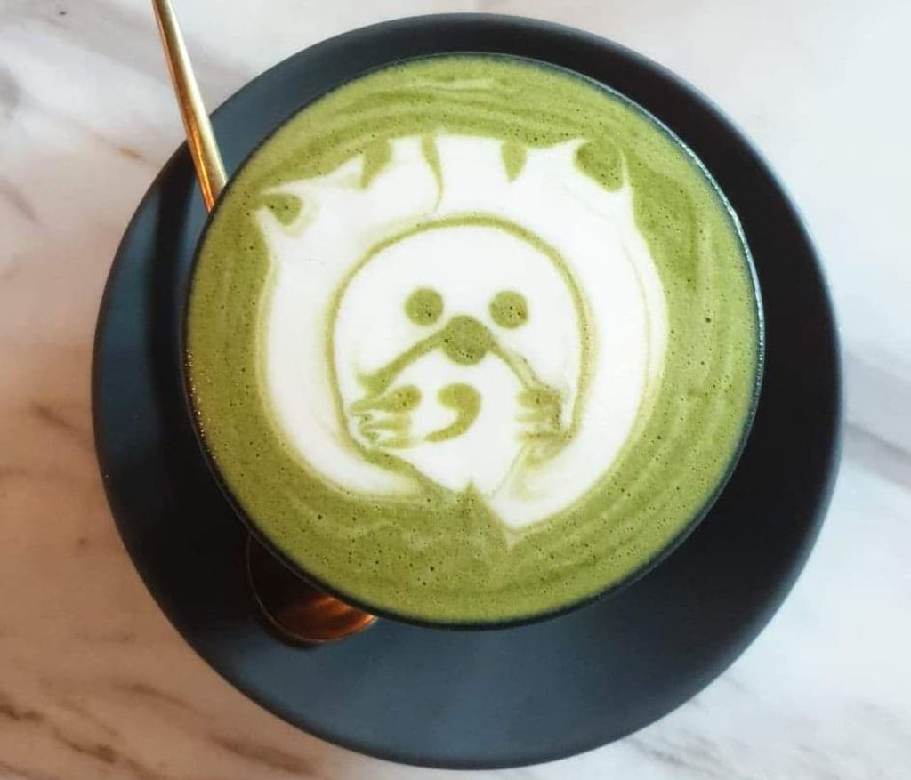 A green latte with a lion drawn in the foam