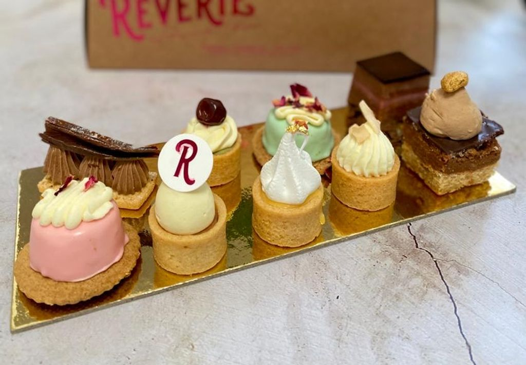 A gold tray with small cakes on it