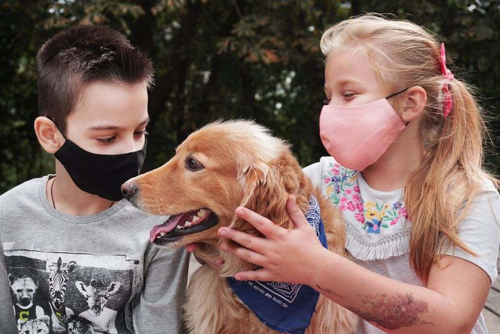 Two kids wearing face masks petting a dog