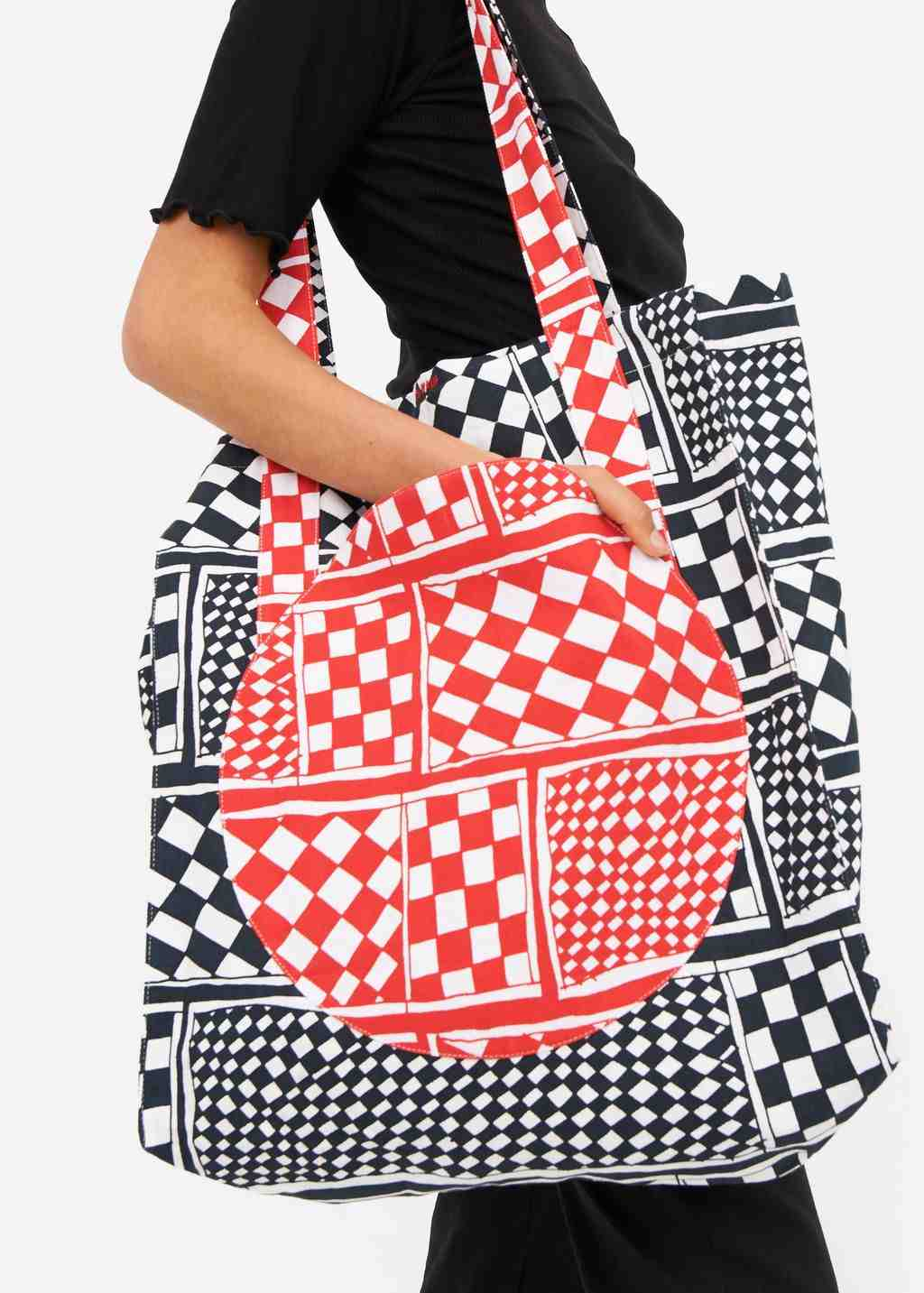 A woman holding a large printed tote bag