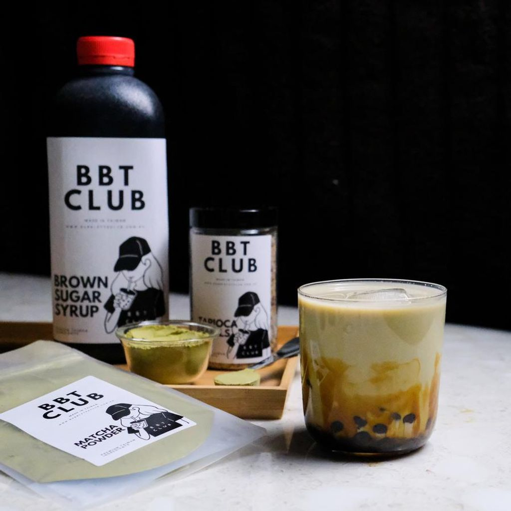 Bottles of syrup and milk tea in a glass