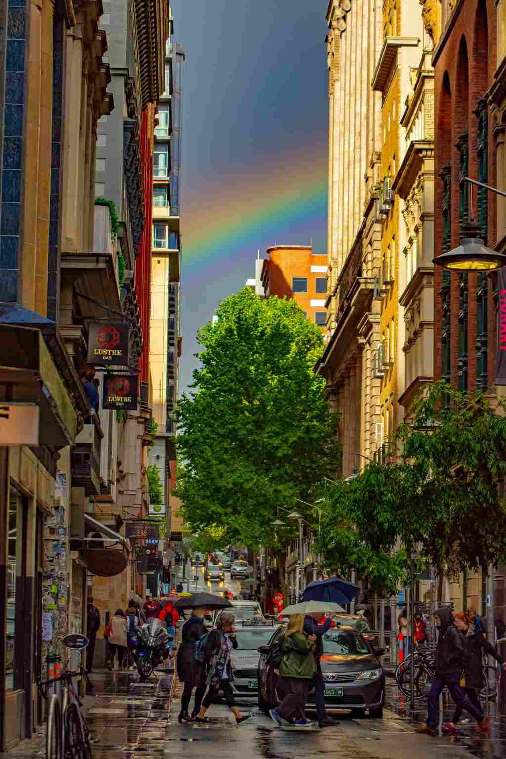 A rainbow in the sky in a city laneway