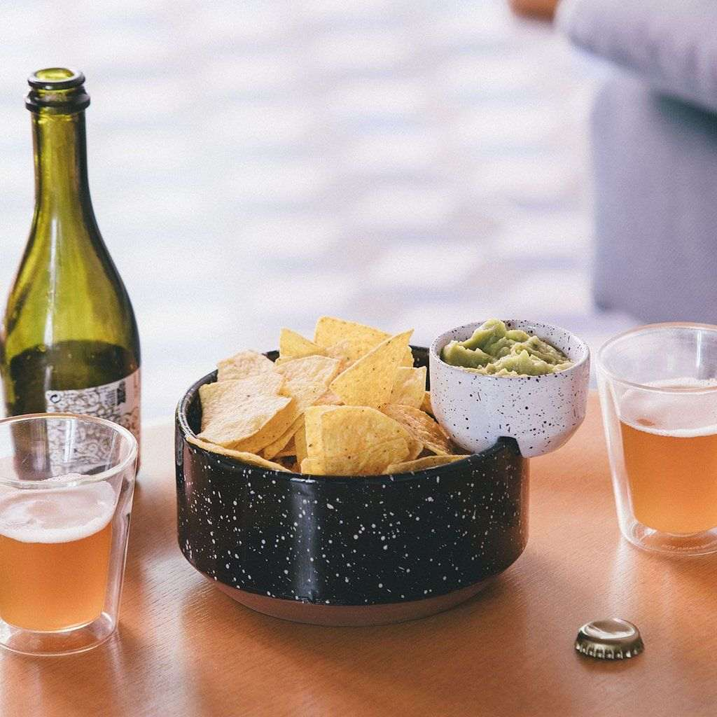 A bowl of corn chips with an attached dipping tray