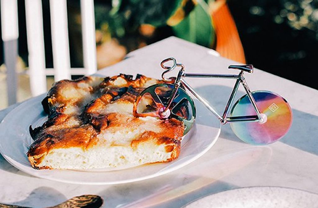 A bike shaped pizza cutter in a piece of pizza
