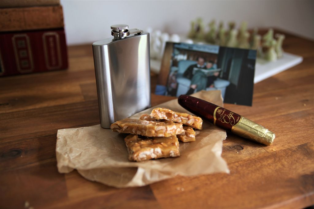 A flask infront of peanut brittle and a cigar on a wooden table