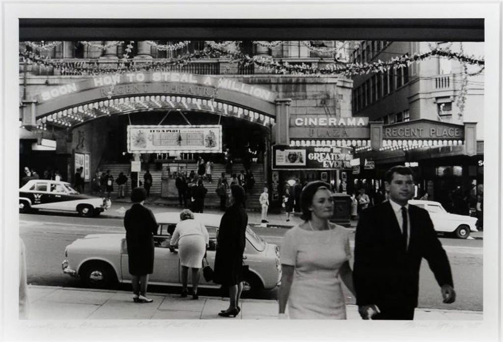 A black and white photo of people milling about outside a theatre